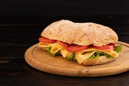 Ciabatta sandwich with lettuce , prosciutto and  cheese on wooden board with copy space. Stock Photo