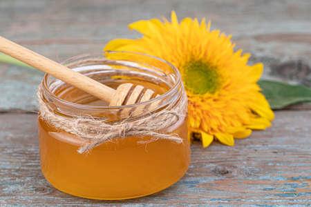 Honey background. Fresh honey in the pot with sunflower flower.