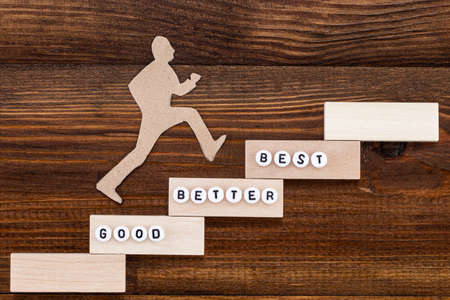 Good - Better - Best, paper man climbing the steps to success in a conceptual image over wooden background.