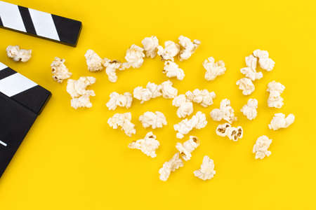 Popcorn and clapperboard on colorful background. Top view. Stock Photo