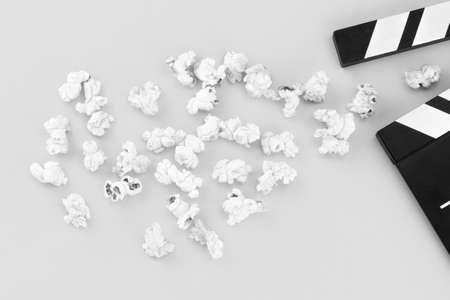 Popcorn and clapperboard on not colorful background