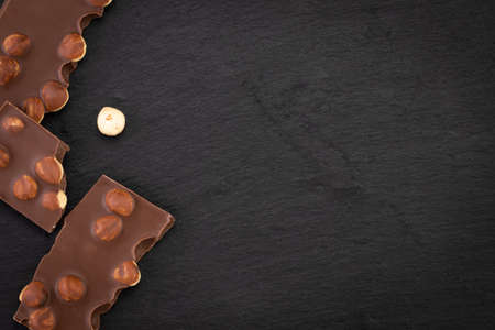 milk chocolate pieces with nuts on a dark background. Top view with copy space. Standard-Bild - 133249044