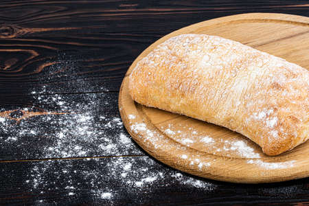 Loaf of ciabatta bread on a cutting board on the dark wooden table. Reklamní fotografie