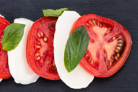Caprese salad. Mozzarella cheese, tomatoes and basil herb leaves over stone table. Top view. Reklamní fotografie