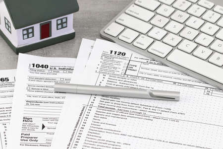 Formulario de impuestos concepto financiero empresarial: formulario de devolución de impuestos con una casa en miniatura. Foto de archivo