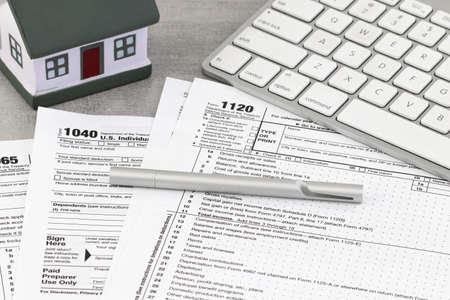 Formularz podatkowy koncepcja finansowa firmy: formularz zwrotu podatku z miniaturowym domem. Zdjęcie Seryjne