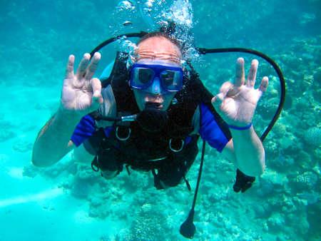 Uomo subacqueo e bellissima barriera corallina colorata sott'acqua.