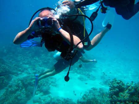 Mann Taucher und schönes buntes Korallenriff unter Wasser.