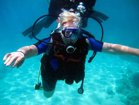 Buzo de mujer y hermoso colorido arrecife de coral bajo el agua. Foto de archivo