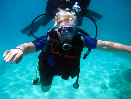 Frauentaucher und schönes buntes Korallenriff unter Wasser. Standard-Bild