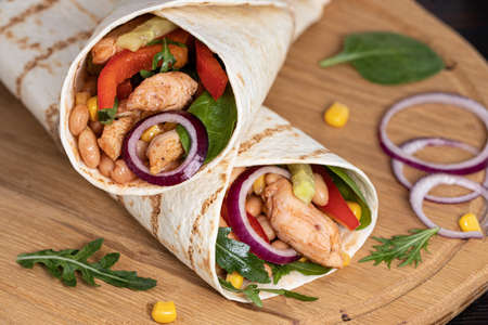 Burritos wraps with chicken and vegetables on dark background. Mexican food.