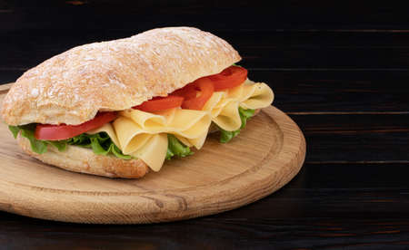 Ciabatta sandwich with lettuce and  cheese on wooden board with copy space. Zdjęcie Seryjne