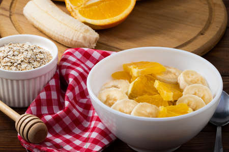 Bowl of oatmeal porridge with banana and orange  on wooden background, copy space.
