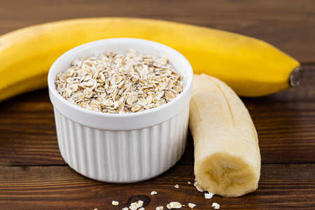 Oatmeal flakes and banana on wooden background, copy space.
