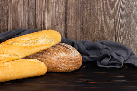 Baked bread and baguette on wooden table