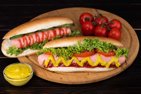 Hot dog with mustard, tomato and lettuce on wooden background.