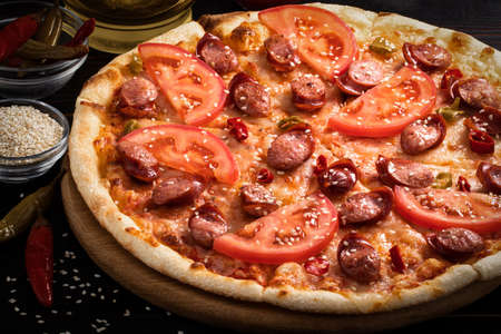 pizza with bavarian sausages, tomato and chili pepper on dark background.