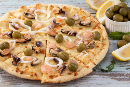 seafood pizza with olives on wooden background.