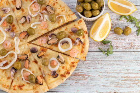 seafood pizza with olives on wooden background. Top view with copy space.