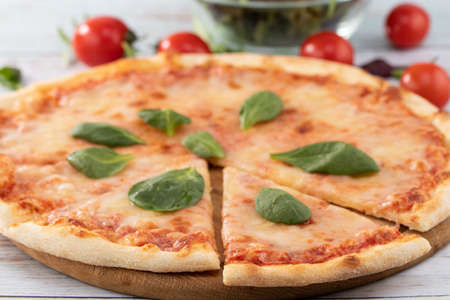 pizza with cheese sauce and spinach on wooden background.