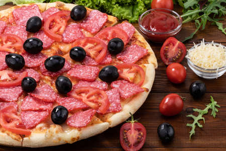 pizza with with pepperoni and olives on wooden background.