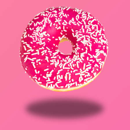 Pink donut with colorful sprinkles on pastel pink background. Sweet donuts.