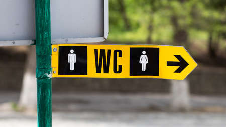 Toilet pointer, wc arrow, restroom icon, green metal sign on pillar in park. Stockfoto