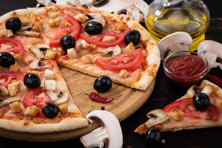 Pizza with chicken, mushrooms and olives on wooden background. Stockfoto