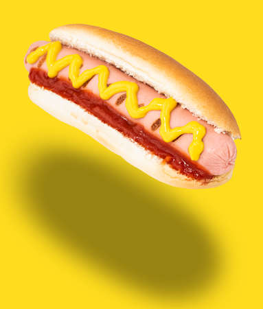 Hot dog with mustard isolated on yellow.