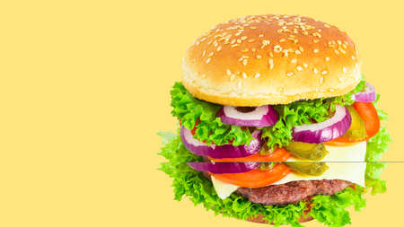 fresh tasty burger isolated on yellow background.  Copy space.
