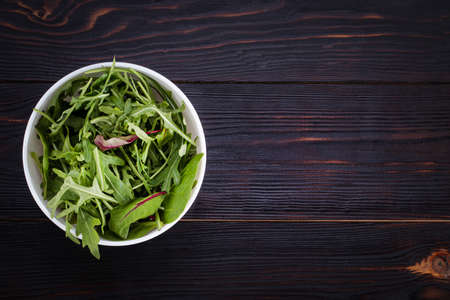 Fresh arugula in bowl, rucola salad on wooden rustic background. Copy space, top view.