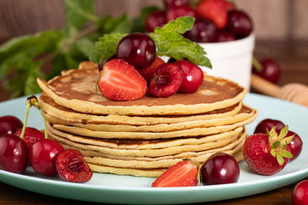 Breakfast. Pancakes with berries on a wooden background.