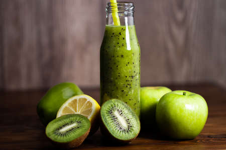 Blended green smoothie with kiwi and green apple on wooden background. Stok Fotoğraf