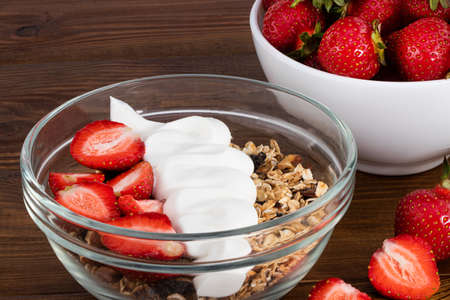 bowl of oat granola with yogurt, fresh strawberry on wooden background for healthy breakfast with copy space.