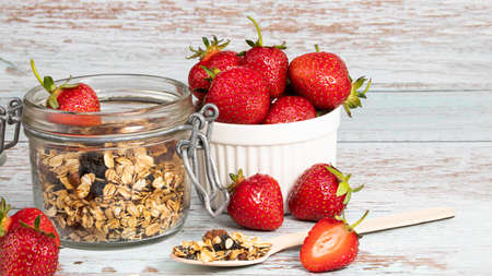 granola with fresh strawberry on white wooden table for healthy breakfast with copy space. Stok Fotoğraf