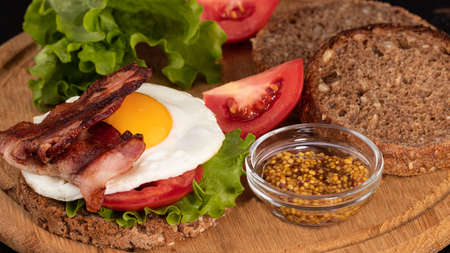 sandwich with egg with bacon, tomatoes and mustard on a dark background. Stok Fotoğraf