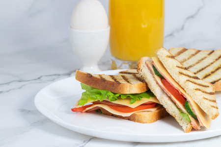 Breakfast with toast with cheese, boiled egg and juice on a light background. Copy space.