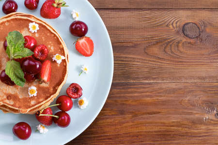 Breakfast. Pancakes with berries on a wooden background. Ð¡opy space, top view. Stok Fotoğraf
