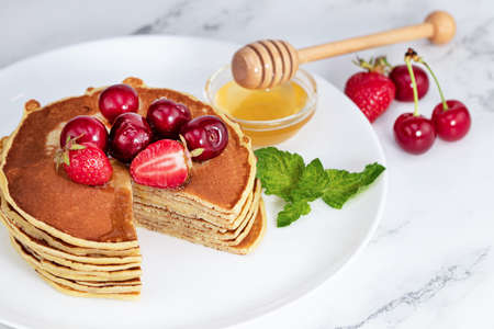 Pancake breakfast. Homemade pancakes with fresh berry and honey,  light  background with copy space. Stok Fotoğraf