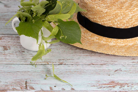 bouquet of linden flowers with a straw hat. Top view, copy space.