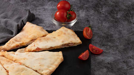 Calzone with tomatoes and ham on dark