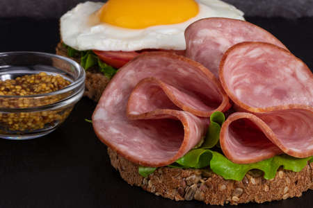 ham and egg bacon sandwich on dark wooden background with copy space. Stok Fotoğraf