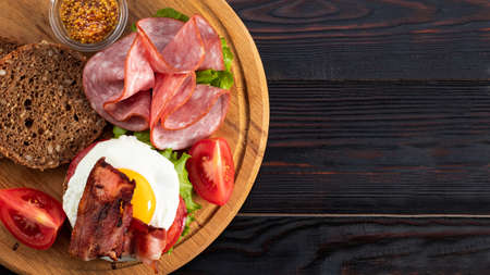 ham and egg bacon sandwich on dark wooden background with copy space. Top view. Flat lay.