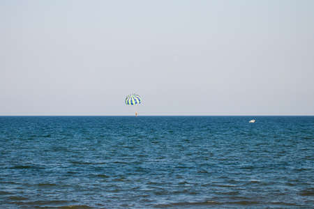 Parasailing outdoor activities at sea. A parachute flies behind the boat over the sea. Sailing.