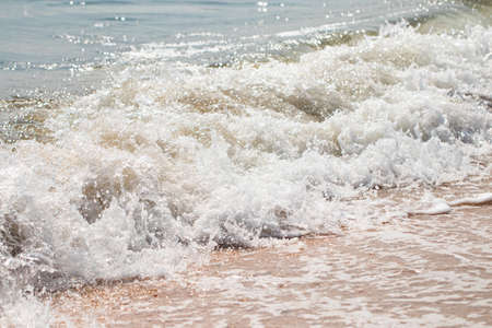 foaming sea wave on a sandy beach. Summer sea background.