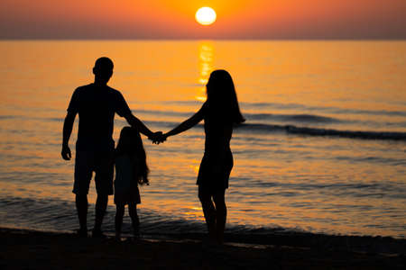 Dad, mom and daughter are watching the sunrise at sea. Family on vacation. Stok Fotoğraf