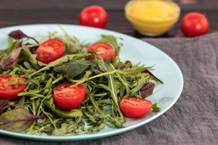 arugula salad and tomatoes on a wooden background. Stok Fotoğraf