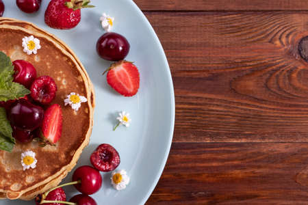 Breakfast Pancakes with berries on a wooden background. Ð¡opy space, top view.