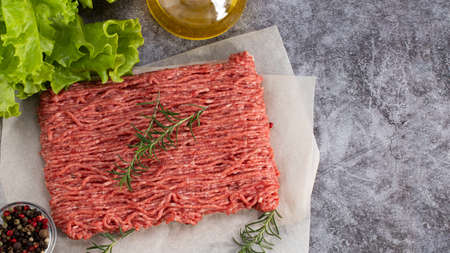 raw minced meat and spices on dark background, top view.