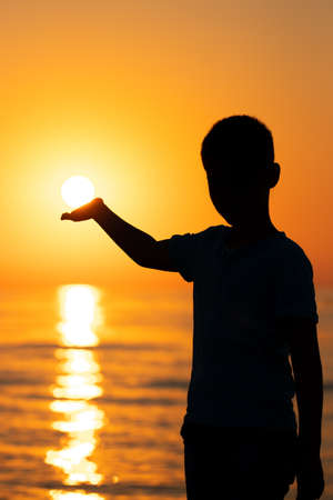 The boy meets the dawn by the sea. The boy raised his hand as if holding the rising sun. Stok Fotoğraf